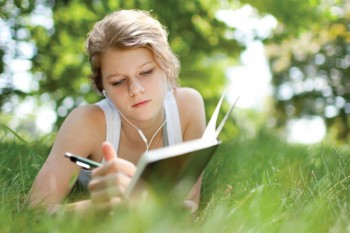 Girl lounging in the grass doing homework.