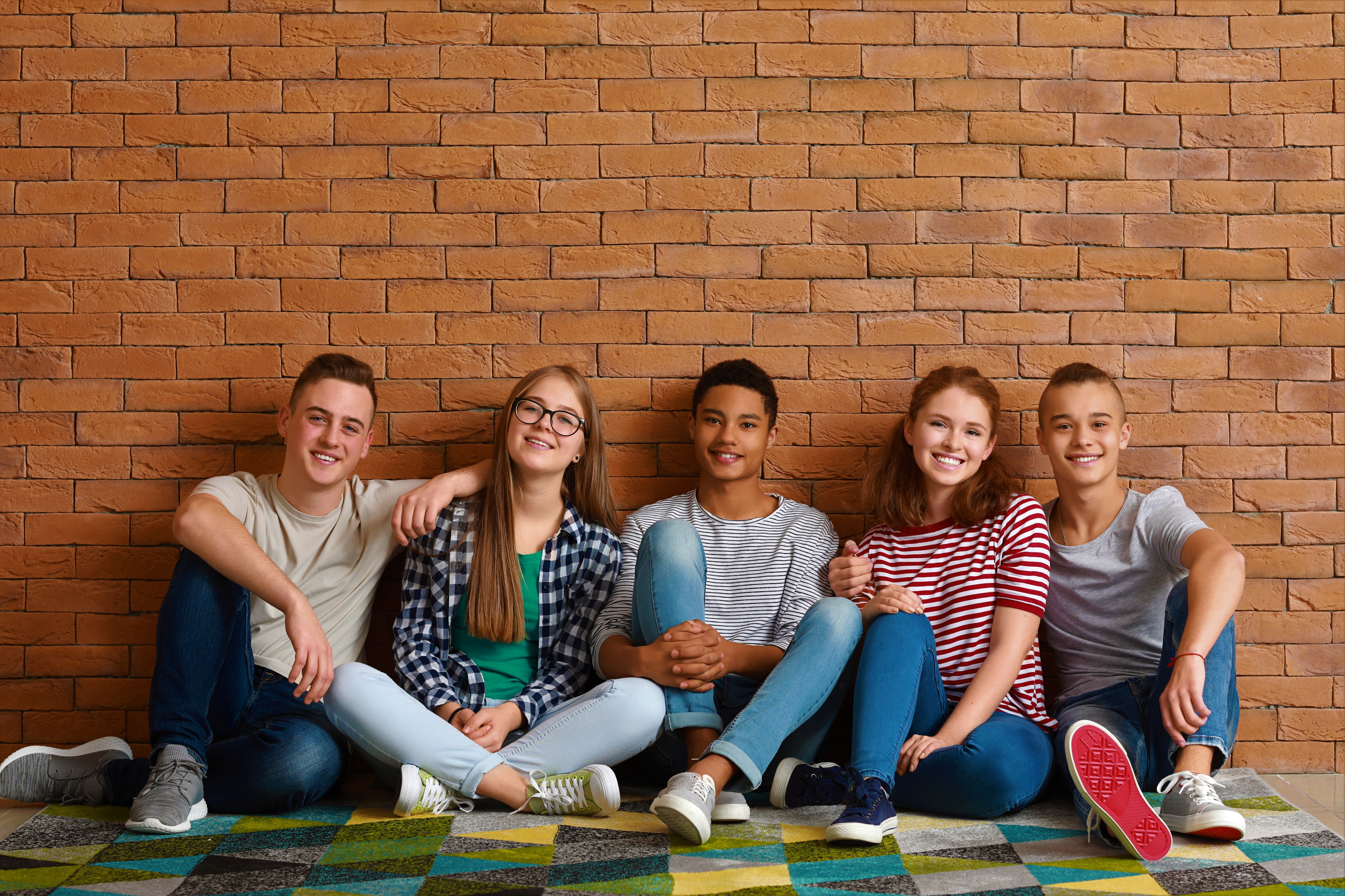 Teens sitting against wall.