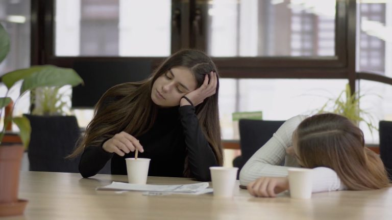 Two girls wasting time drinking coffee